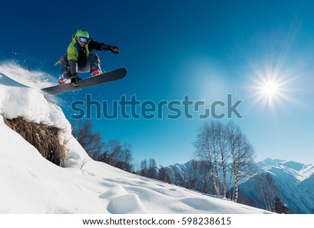 snowboarder is jumping with snowboard from snowhill #598238615