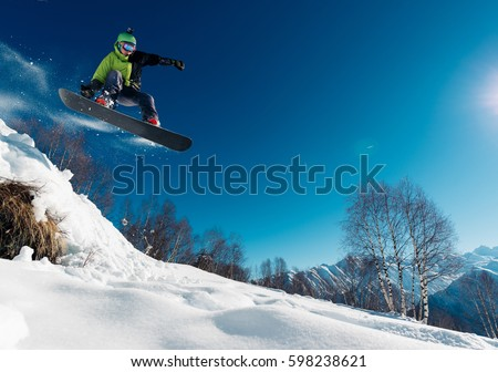 snowboarder is jumping with snowboard from snowhill #598238621