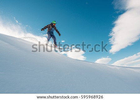 snowboarder is riding with snowboard from powder snow hill or mountain very fast #595968926