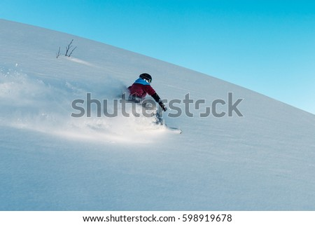 snowboarder is riding with snowboard from powder snow hill or mountain very fast #598919678