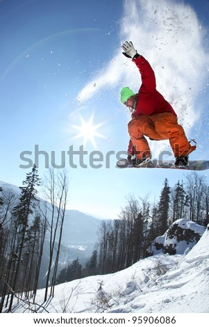 Snowboarder jumping against blue sky  and sun rays