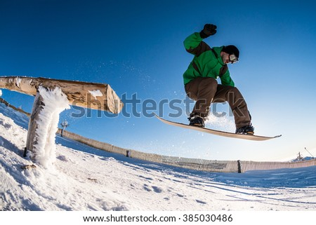Snowboarder jumping from a wood rail against blue sky.