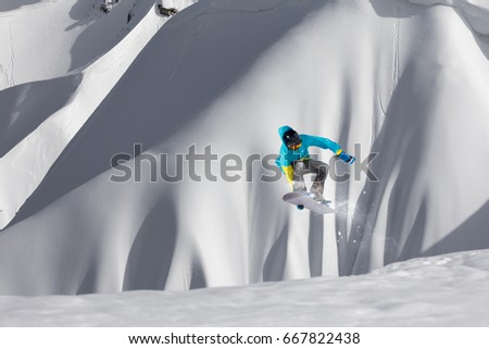 Snowboarder jumping in the mountains. Extreme sport.
