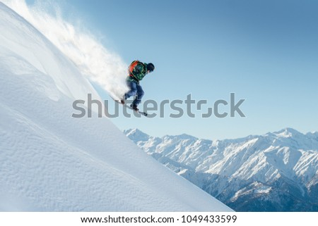 snowboarder jumping on a steep mountainside #1049433599