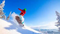 Snowboarder jumping through air with deep blue sky in background, Freeride winter forest.