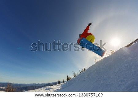 Snowboarder jumping through air with deep sunset sky in background #1380757109