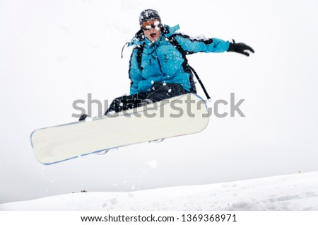 Snowboarder jumping through air with gray sky #1369368971