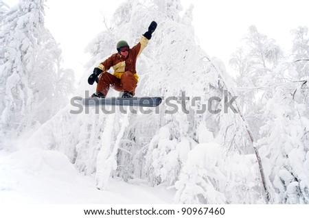 Snowboarder jumping through air with white forest in background