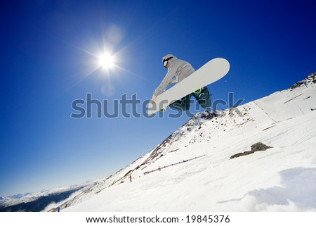 Snowboarder jumps in air with blue sky background - stock photo