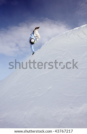 Snowboarder jumps in air with blue sky background #43767217