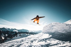 Snowboarder jumps in the air right in front of the sun