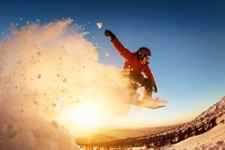 Snowboarder jumps or flies against sunset light with snow dust