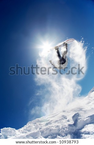 Snowboarder launching off a jump; La Thuile , Aosta, Italy.