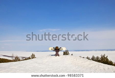 Snowboarder lies on the bench. Against the backdrop of beautiful mountain  landscape of winter. A sunny day.
