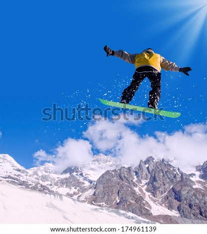 Snowboarder making jump high in clear sky #174961139