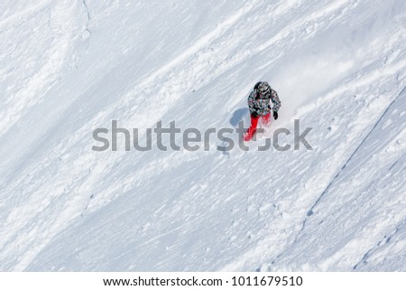 Snowboarder on the way down in winter mountains, Gudauri, Georgia #1011679510