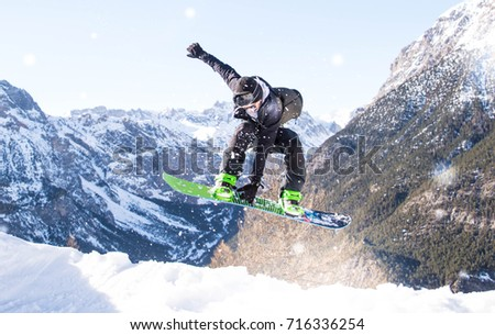 Snowboarder performing tricks on the snow with dramatic background #716336254