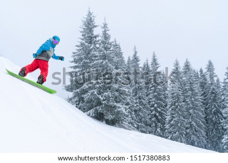Snowboarder rides from powder snow hill. Mountain freeride snowboarding. Winter Carpathians #1517380883