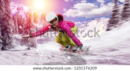 snowboarder rides her snowboard downhill with high speed through fresh snow. she wears pink and green ski outdoor gear. freestyle risky race.