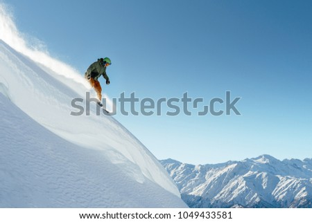 snowboarder rides on a steep mountainside on a beautiful landscape #1049433581