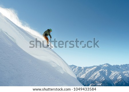 snowboarder rides on a steep mountainside on a beautiful landscape #1049433584