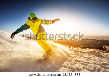 Snowboarder rides on the slope on sunset backdrop. Sheregesh resort, Siberia, Russia