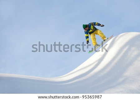 snowboarder riding in half-pipe - stock photo