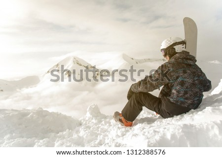 Snowboarder sit with snowboard in hands sits on big rock on mountains backdrop. Bansko, Bulgaria free ride concept #1312388576