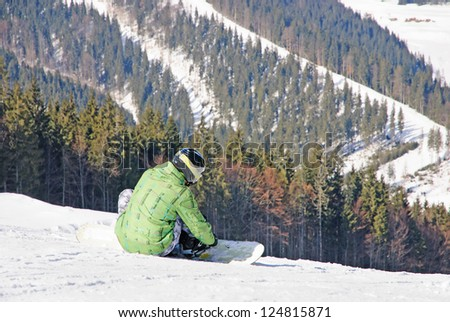 snowboarder sitting on snow against mountains and fir forest