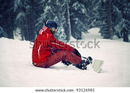 Snowboarder sitting on the snow and watching beautiful nature