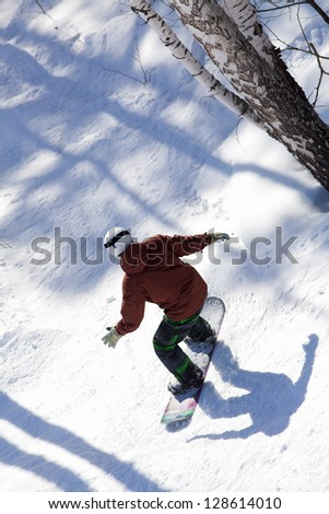 snowboarder slides from the mountain through the forest along the road extreme