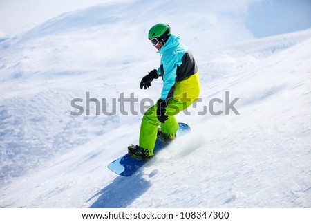 Snowboarder sliding down a slope on a sunny day