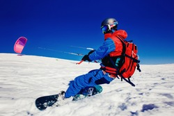 Snowboarder. Snowboard with snow kite against a blue sky. Concept outdoor extreme activities in winter snowkite
