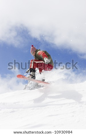 snowboarder taking jump in fresh snow