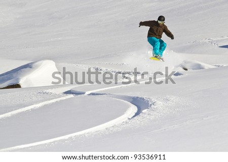 Snowboarder uses snowcovered rock for a jump