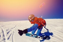 Snowboarder with a kite on fresh snow in the winter in the tundra of against a clear blue sky. Teriberka, Kola Peninsula, Russia. Concept sports snowkite.