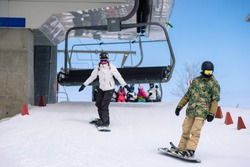 Snowboarders disembark from a chairlift