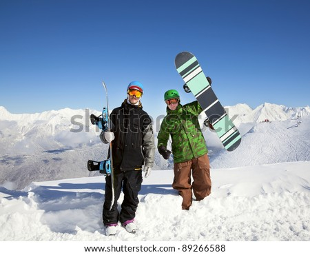 Snowboarders on top of a mountain overlooking a beautiful panorama