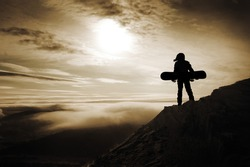 Snowboarders silhouette stands over the clouds