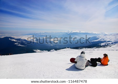 snowboarders sitting on snow and see at mountains