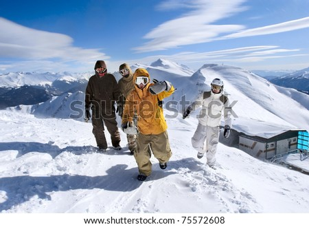 Snowboarders walking along the ridge of the mountains
