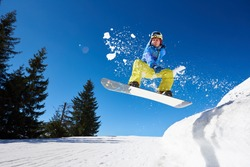 Snowboarding closeup in jump on blue sky background. Portrait of young man snowboarding in winter. Ski season and winter sports concept