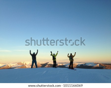 Snowboarding concept. Winter sports concept with group of friends. Snowboarders having fun on top of the mountains. Boarders at sunset. Happy riders.  Snowboarders silhouette #1011166069