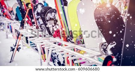 Snowboards and skis kept together at ski resort