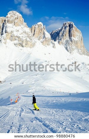 Snowborder going down the slope at Val Di Fassa ski resort in Italy