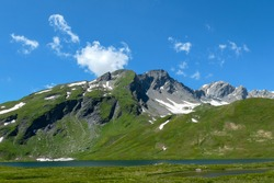 Snowcapped peaks above green pastures in summer. View of a lake at the bottom of the valley with meadows. Mountains of the Italian Alps.
