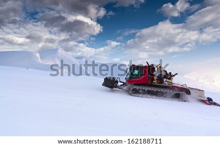 Snowcat with people going up the hill.