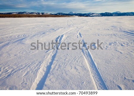 Snowdrift over vehicle tire tracks in deep snow on surface of frozen lake leading to distant shore on sunny winter day. - stock photo