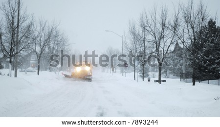 Snowed street with snow-plowing truck