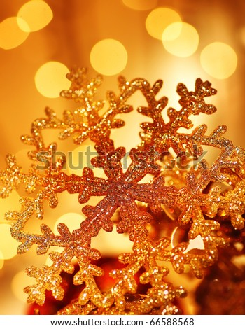 Snowflake background golden Christmas tree ornament and holiday decoration over abstract defocus lights - stock photo